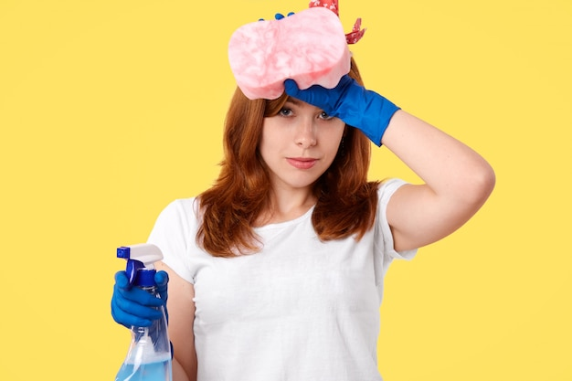 Hygiene and cleaning concept. tired onworked female in rubber gloves and white t shirt, feels fatigue after doing house duties, rubs forehead, holds cleanser and sponge, isolated on yellow wall