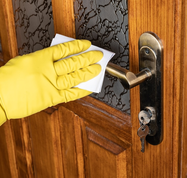Hygiene and healthcare concept. man hand in gloves spraying alcohol sanitizer to the door handle against corona virus disease (covid-19)