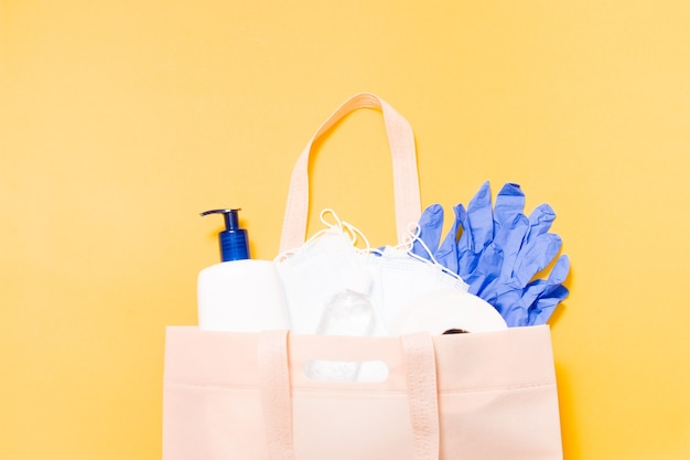 Hygiene products in a fabric bag on a yellow background, protective masks, liquid soap, toilet paper