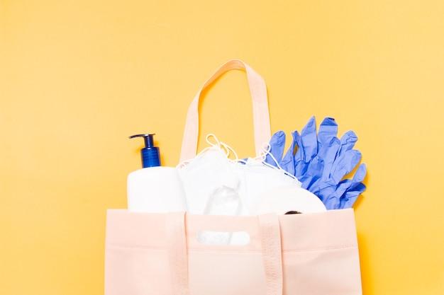 Средства гигиены в тканевом мешочке на желтом фоне, защитные маски, жидкое мыло, туалетная бумага