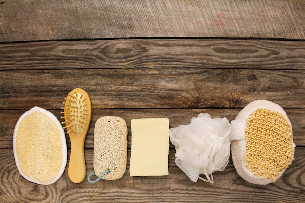 Hygiene products: soap,comb, sponge, pumice stone on old wooden background.