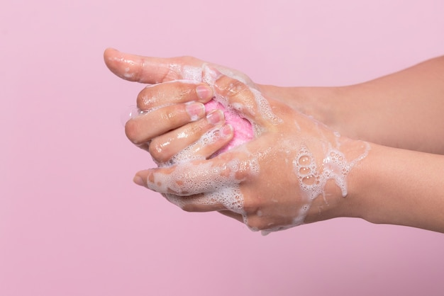 Hygiene to protect human health from viruses hand washing with soap process on pink