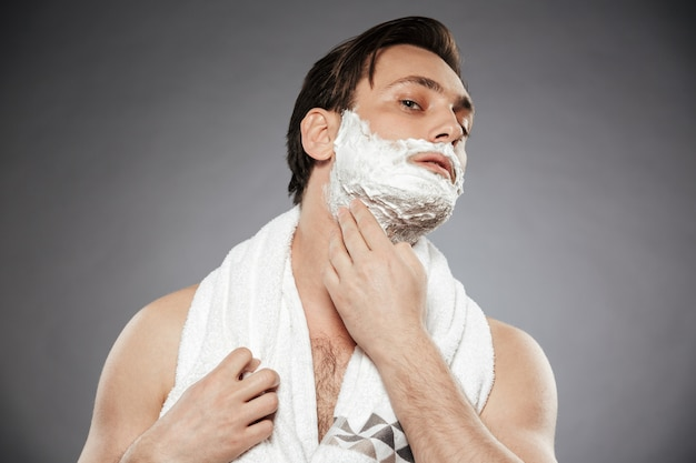 Hygiene and skin care of adult guy with towel on neck putting shaving foam on face, isolated over gray wall