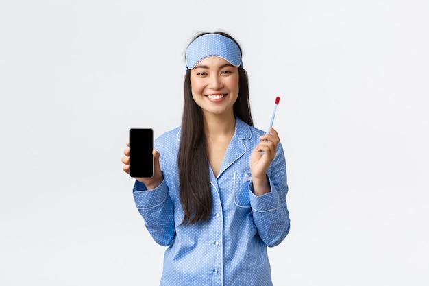 Гигиена, технологии и люди дома концепции. довольно женственная азиатская девушка в синей пижаме и спальной маске держит зубную щетку, показывая белую улыбку и экран смартфона, белый фон