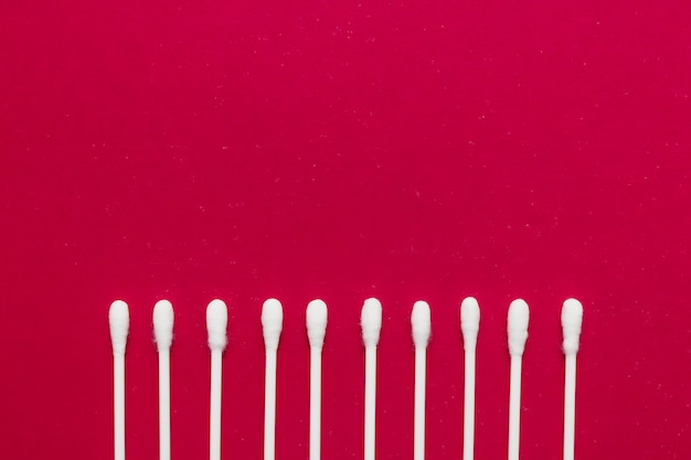 Hygienic, cotton buds on a red background.
