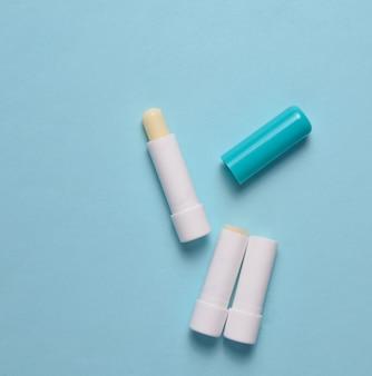 青いパステル背景、上面図、ミニマリズムに衛生的な口紅
