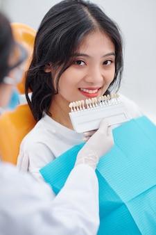 초음파 치과 청소 직후 웃는 여성 환자의 치아 색상을 확인하는 팔레트가 있는 위생사