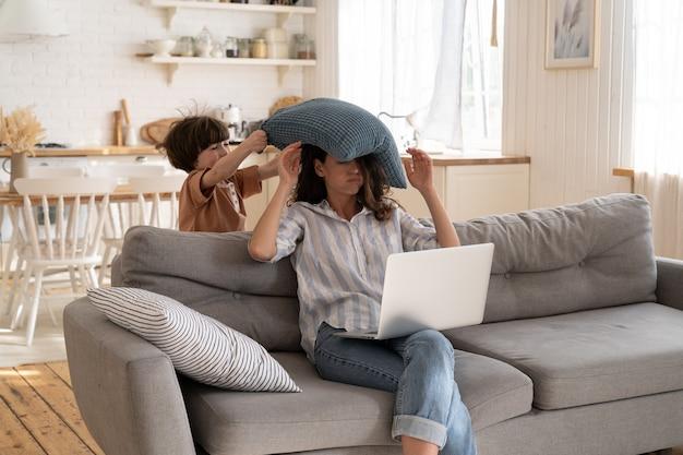 지나치게 활동적인 어린 아이가 베개를 베고 노트북으로 엄마를 때렸다. 젊은 여성 기업가가 집에서 일하려고 한다