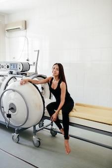 Камерный резервуар для гипербарической оксигенотерапии (hbot) используется для специализированного лечения травм в больничной клинике. внешнее смотровое окно и манометр с подушкой и кроватью внутри.