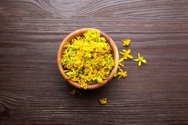 Hypericumperforatumまたはセントジョンズ麦汁植物花のつぼみを暗い背景、上面図の木製ボウルに