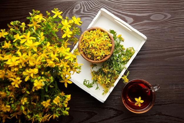 Бутоны цветов завода зверобоя продырявленного с травяным напитком на деревянном столе
