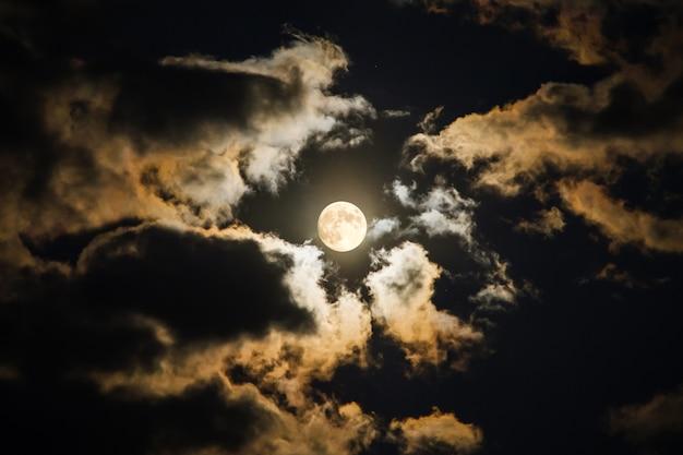 Hypnotizing full moon on dark sky glowing between clouds