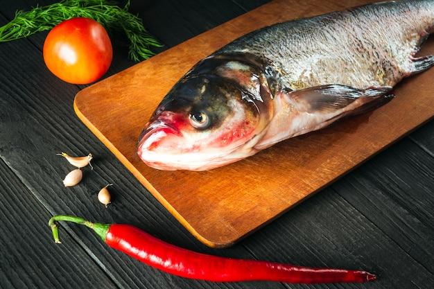 Hypophthalmichthys 또는 큰머리 잉어는 요리하기 전에 야채와 함께 커팅 보드에 있습니다. 레스토랑 주방에서 껍질을 벗긴 생선. 생선 다이어트 아이디어
