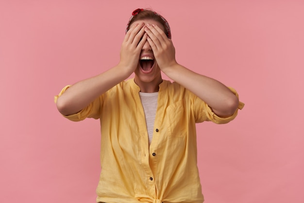 머리에 머리띠와 노란색 셔츠에 히스테리 분노 젊은 여자는 손으로 눈을 덮고 분홍색 벽을 통해 소리
