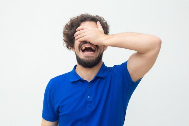 Истеричный парень, закрывающий глаза и лицо