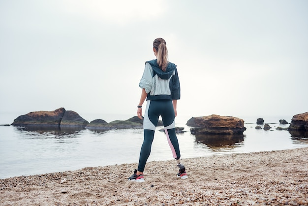 Обожаю жить у моря, вид уверенной в себе спортивной женщины-инвалида в спортивной одежде.