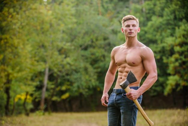 私は犯罪者です。斧を持つ筋肉の男。セクシーなマッチョな裸の胴体の斧。残忍で魅力的な木の男性。ボディービルダーは彼の筋肉を示しています。力と強さ。木こりは斧を運びます。男強い体。