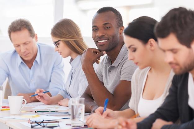 Я часть сильного и творческого коллектива. группа деловых людей, сидящих в ряд за столом, в то время как красивый африканский мужчина смотрит в камеру и улыбается