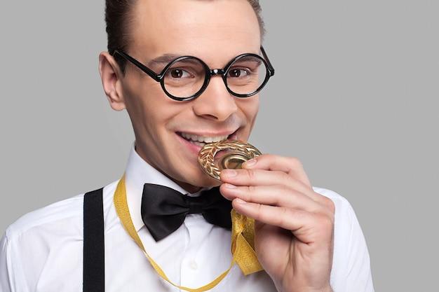 Я победитель! веселый молодой человек в галстуке-бабочке держит золотую медаль и кусает ее, стоя на сером фоне