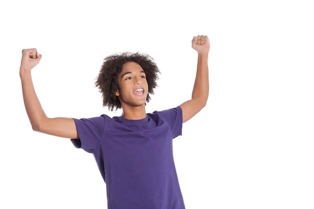 私は勝者です!白で孤立して立っている間腕を上げたままで幸せなアフリカの10代の少年