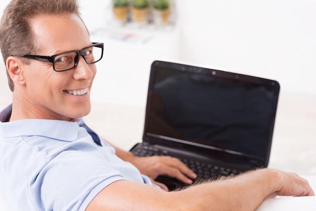 私はいつもオンラインです。ラップトップで作業し、自宅のソファに座って肩越しに見ている陽気な成熟した男の上面図