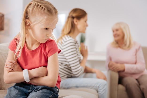 Я зол. милая грустная молодая девушка отворачивается от матери и расстроена из-за того, что ей не разрешают играть