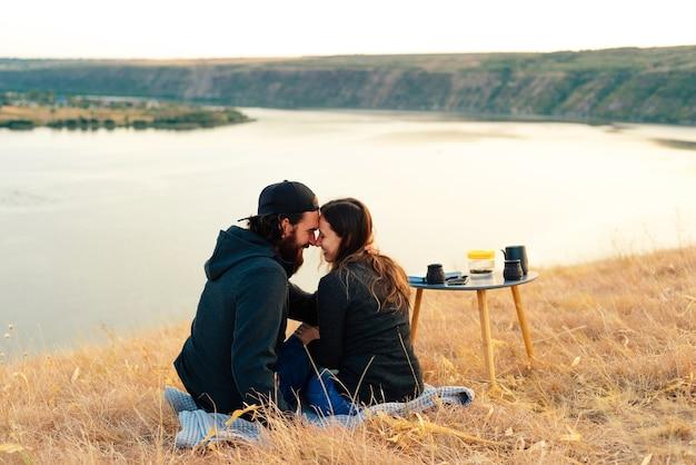 私は川の近くでピクニックをしている美しい若いカップルです