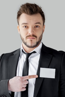 I am a big boss here. young and bossy man in formalwear looking at camera and pointing his badge while standing against grey background