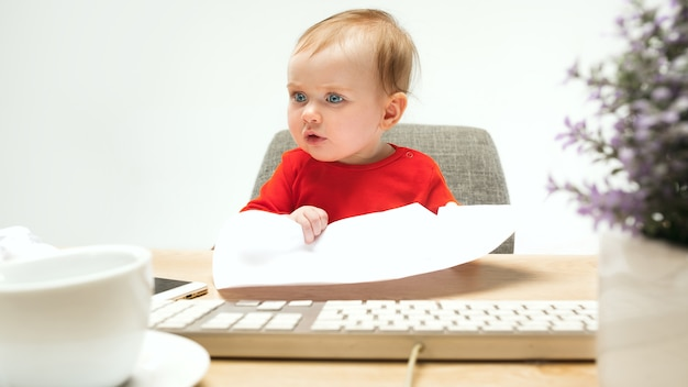 I am boss. child baby girl sitting with keyboard of modern computer or laptop in white studio