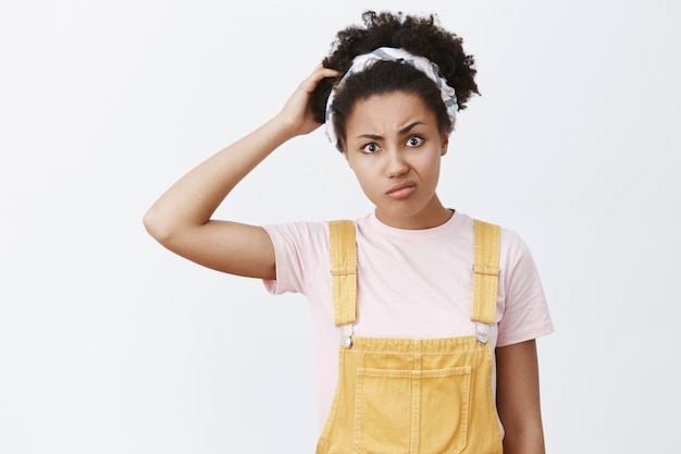 I am confused. portrait of unsure doubtful cute african american young woman in yellow overalls and headband, scracthing head, pursing lips and frowning while thinking, being questioned and uncertain