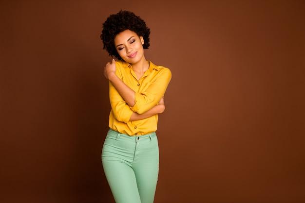 私はかわい子ちゃんです!目を閉じて肩を抱えている美しい暗い肌の女性の写真は、自分自身を愛している自分自身を楽しんでください黄色のシャツを着ています緑のズボンは茶色の色を分離しました