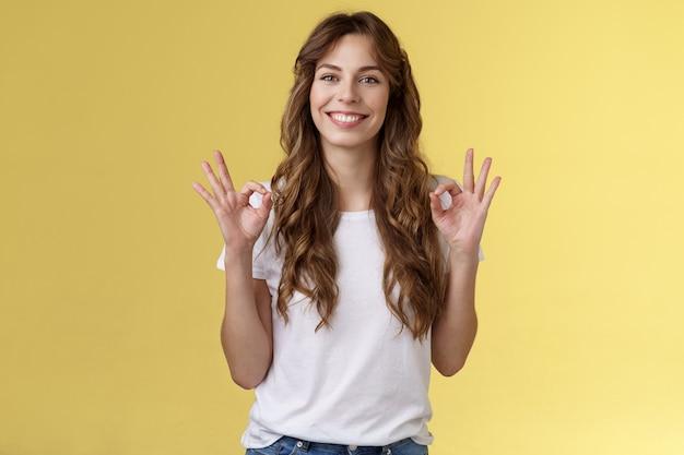 Я в порядке, спасибо за вопрос. веселая, расслабленная улыбающаяся симпатичная кавказская женщина показывает жест колец в порядке, довольна, отличное состояние, рекомендую, идеальную компанию, услуги, стенд, желтый фон