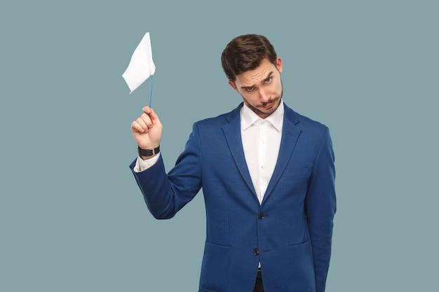 Я сдаюсь. грустный неудачник бизнесмен в синей куртке и белой рубашке, стоящий и держащий белый флаг и смотрящий в камеру с грустным лицом. крытый, студийный снимок, изолированные на светло-синем фоне.