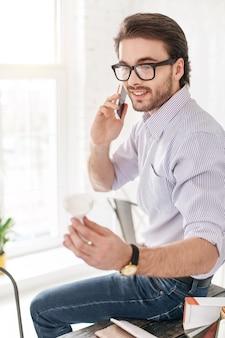 나는 행복하다. 테이블에 앉아있는 동안 전화로 얘기하는 쾌활한 수염 난된 남자