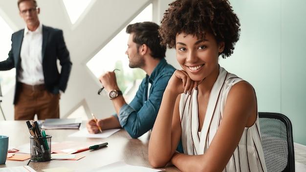 Я счастлив работать здесь, молодая афроамериканская женщина смотрит в камеру и