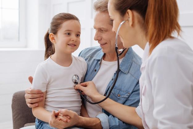 Я здесь для тебя. сладкая довольная бесстрашная девушка сидит на коленях у отца, потому что не боится, пока доктор глубоко слышит ее дыхание