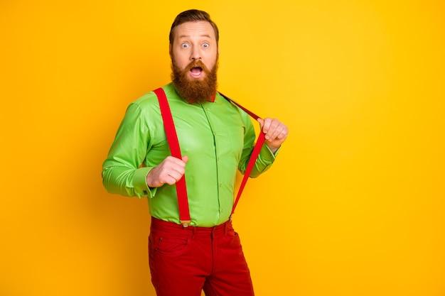Мне жарко! фото восхищенного парня с открытым ртом, крутой элегантный образ в стиле фанк на вечеринке, держитесь за руки, подтяжки, в ярко-зеленой рубашке, красные брюки с галстуком-бабочкой, изолированные на белом цвете