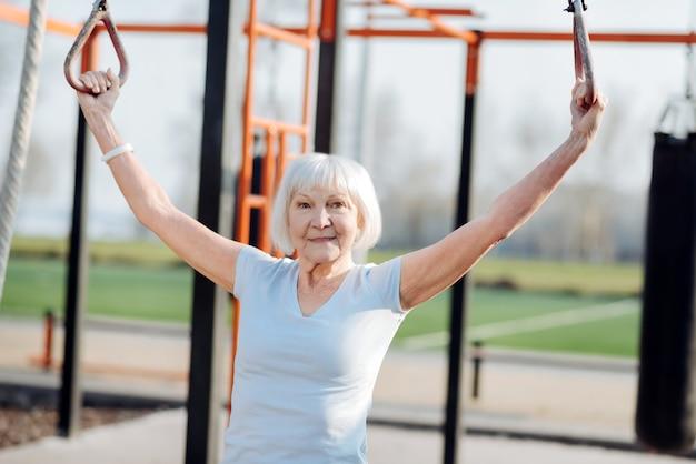 私は刺激を受けています。野外で運動しながらチンアップをしているうれしそうなブロンドの女性