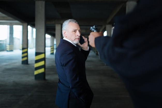 Меня похитили. несчастный унылый хороший бизнесмен разговаривает по телефону и смотрит на пистолет во время похищения