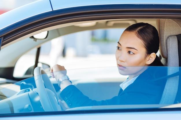 私は遅刻だ。車で運転しながら時計を見ている素敵な楽しい女性