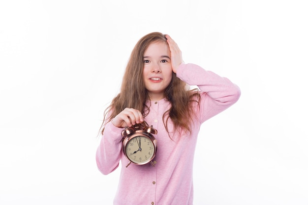 Я опаздываю, школьница держит будильник и жестикулирует