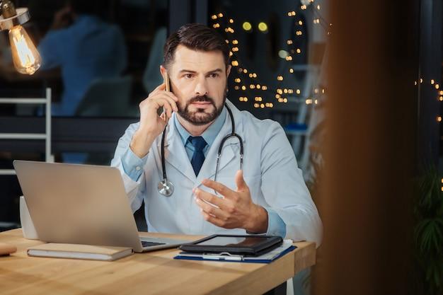 聞いている。真面目なプロの男性医師が電話を耳に当て、電話を受けながら対話者の話を聞いている