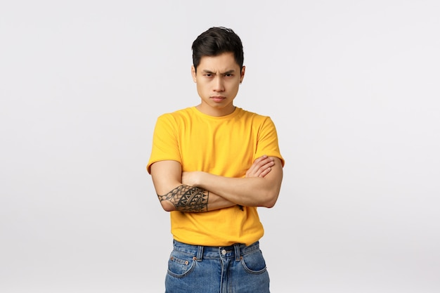 I am mad at you. angry and displeased, offended defensive asian man in yellow t-shirt, cross arms over chest, frowning sulking and look from under forehead insulted, white wall