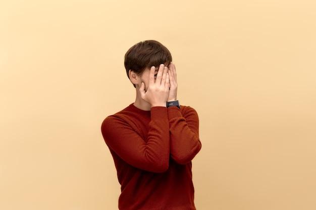 나는 여기에 없다. 스웨터를 입고 수염을 가진 수줍은 젊은이의 사진은 손바닥으로 얼굴을 덮고 베이지 색 벽에 포즈를 취하는 그의 손가락을 통해 피킹합니다.