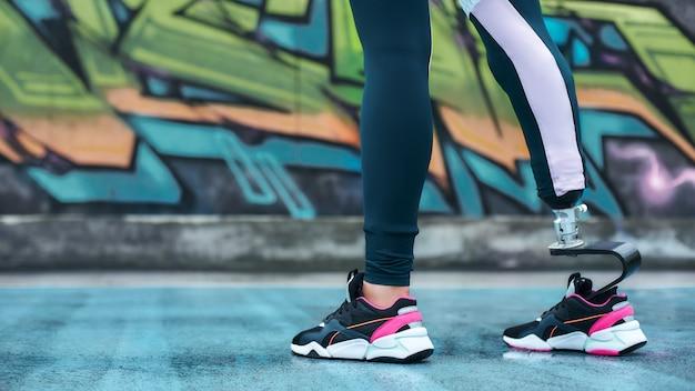 Неслабое обрезанное изображение молодой женщины-инвалида в спортивной одежде с бионической ногой