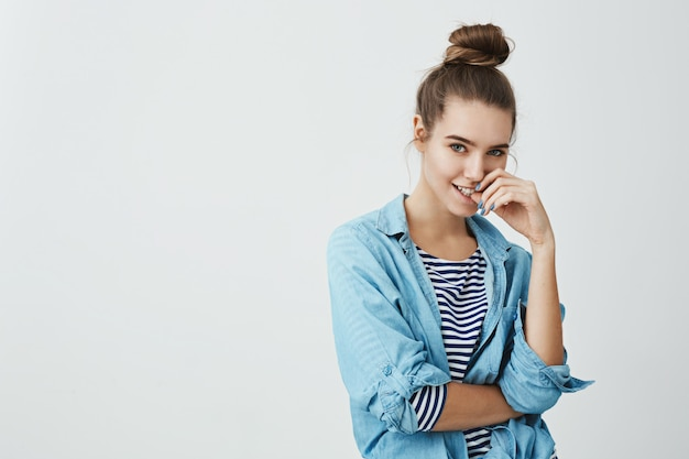 I am planning to make you mine. portrait of cute curious woman in bun hairstyle, holding fingers on lip and looking with thoughtful and positive expression, thinking up plan or having idea