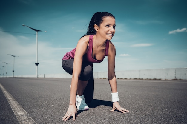 I am ready!  beautiful woman in sports shoes standing in starting line and smiling