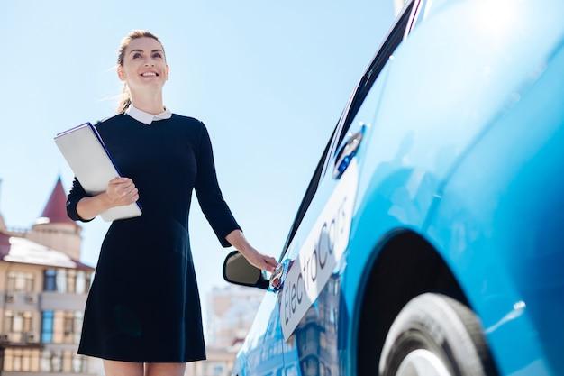 準備ができています。車のドアを開けて、重要な書類を持って笑っている陽気なスマートポジティブ実業家