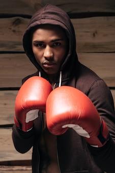 私は戦う準備ができています。フード付きシャツとボクシンググローブで自信を持って若いアフリカ人