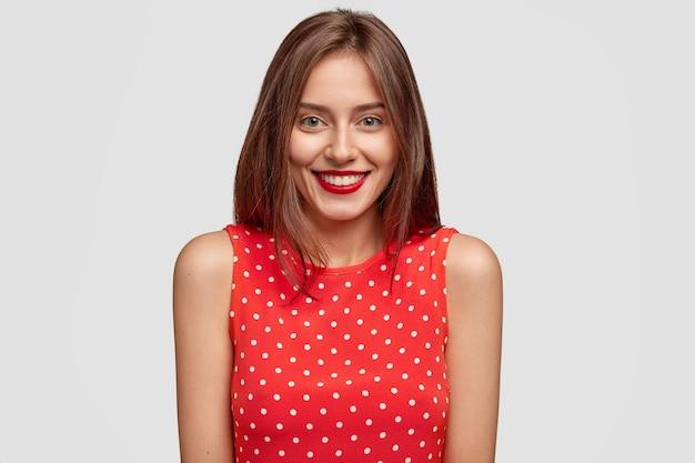나는 당신의 아이디어를들을 준비가되어 있습니다. 우아한 옷을 입은 행복한 학생, 붉은 입술, 매력적인 미소가 있습니다.